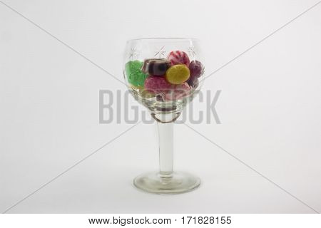 Images of colored caramel sweets in glass vase, image isolated on a white background