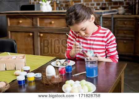 Cute little girl painting easter egg at wooden table