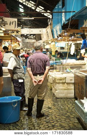 TOKYO-JAPAN, 27 June 2016: Japanese men standing in tsukiji fish market in Tokyo, japan. The biggest wholesale fish and seafood market in the world.