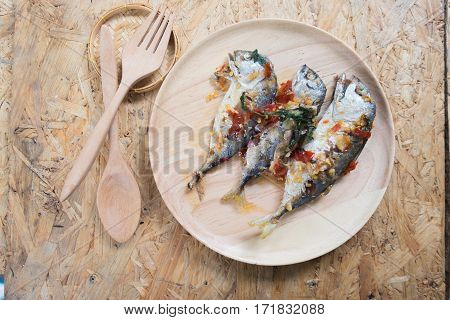 Mackerel fish fried topped spicy curry on wood dish Thai style food