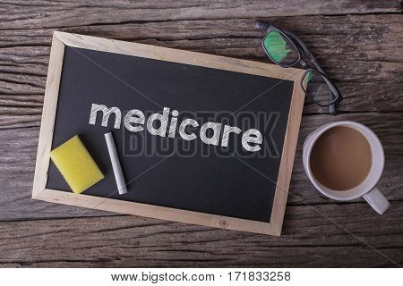 Medicare On Blackboard With Cup Of Coffee, With Glasses On Wooden Background.