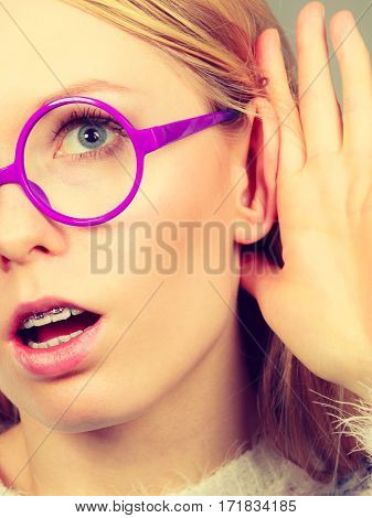 Rumors gossip and gestures concept. Nerdy blonde woman listening carefully with hand close to ear