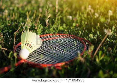 Shuttlecock and badminton racket on green grass. Summer Games.