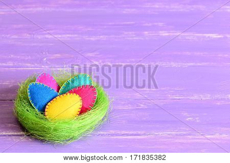 Easter eggs crafts in a nest. Colorful felt Easter eggs in a green sisal nest isolated on purple wooden background with copy space for text. Bright Easter background