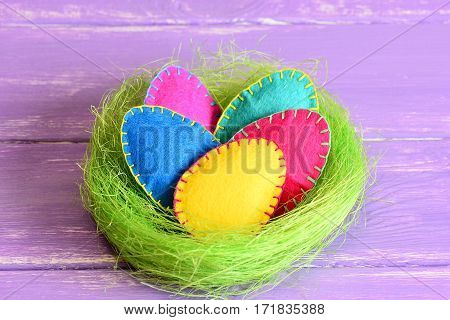 Easter eggs in a nest. Bright felt Easter eggs in a green sisal fibre nest isolated on purple wooden background. Simple and adorable Easter decorating idea for home. Closeup