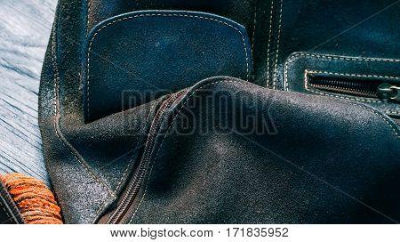 Brown nubuc leather backpack upside down on black wood