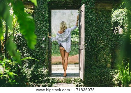 Young beautiful woman standing in door space of garden outdoors during daytime
