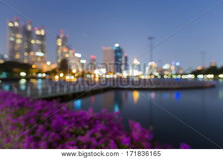 Night blurred lights city office building with reflection in public park abstract background