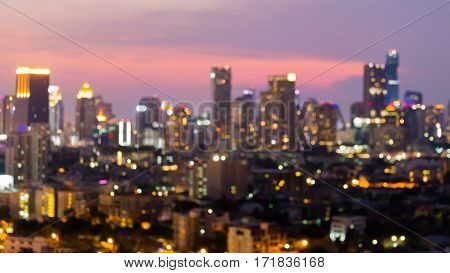 Night blurred bokeh lights city business area with twilight sky after sunset abstract background