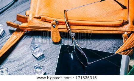 Summer fashion set with orange handbag, sunglasses and ice cubes