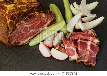 Smoked Pork Bacon With Vegetables And Herbs On A Kitchen Dark Wooden Table
