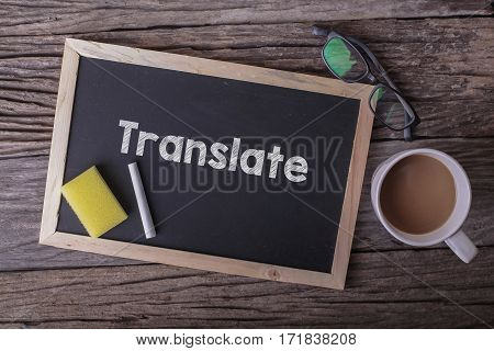 Translate On Blackboard With Cup Of Coffee, With Glasses On Wooden Background.