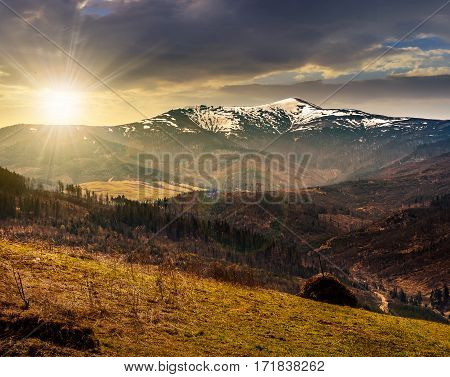 Agricultural Field With Haystack On Hillside At Sunset