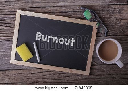 Burnout On Blackboard With Cup Of Coffee, With Glasses On Wooden Background.