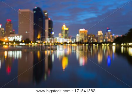 Twilight blurred bokeh lights office building with reflection over water lake abstract background