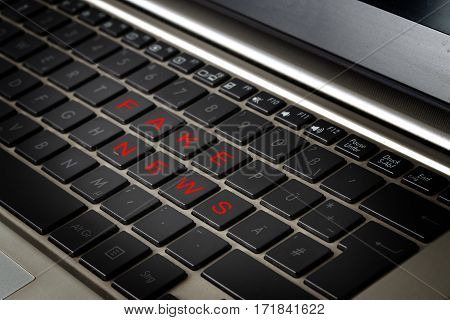 Computer laptop keyboard with the words FAKE NEWS in red letters on black keys selected focus narrow depth of field