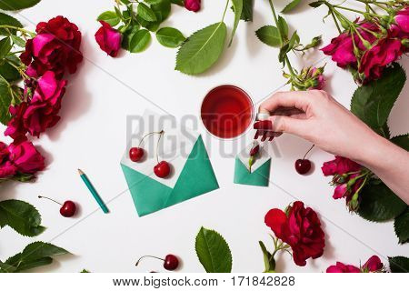 Female hand with red fingernails holding a cup of tea red tea ripe cherries small envelopes roses lay on a white background. Tea drinking during work. Healing drink. Berry compote. Flat lay