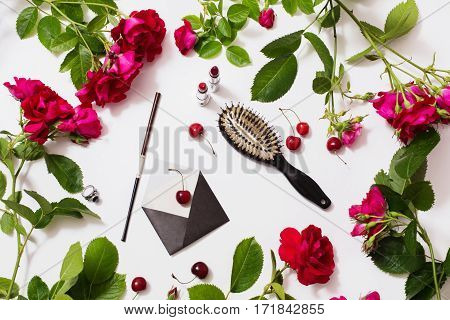 Mouthpiece hairbrush lipstick ring ripe cherries small envelopes roses with green leaves lay on white background. Flat lay top view. Flower frame. Female boudoir. Workplace