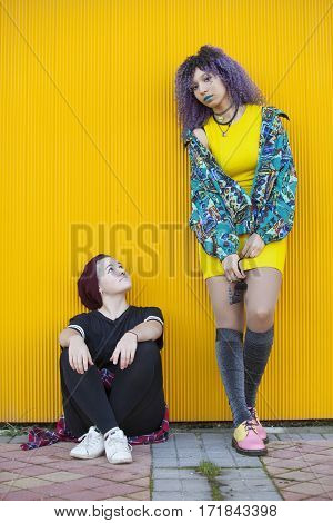 Interracial couple of young hipsters teenagers isolated on yellow background