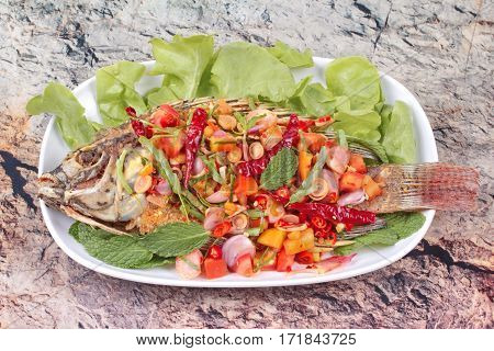 Spicy And Sour Fried Tilapia Salad With Baby Tamarind Leaves .