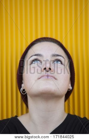 portrait of a thoughtful teen gay woman with a piercing on her nose isolated on yellow background