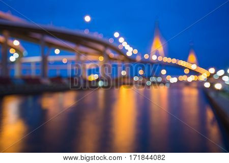 Blurred light city suspension bridge river front with twilight sky background