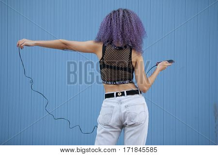 Afro woman listening to music isolated on a blue background