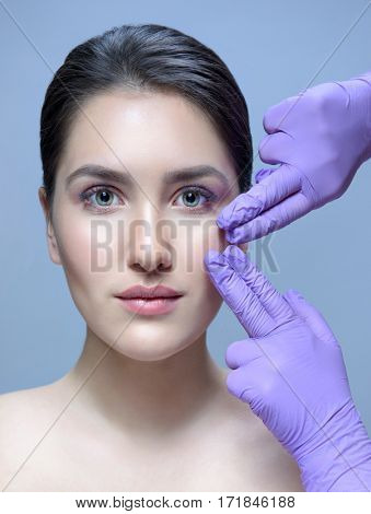 closeup portrait of attractive young caucasian woman brunette  on blue background studio shot lips face  head and shoulders perfect skin care hands gloves lifting plastic
