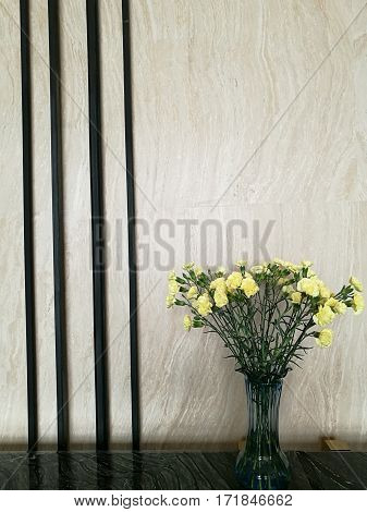 Vase of yellow carnation flower in the right side of marble bar in the hotel lobby with blur background for decoration
