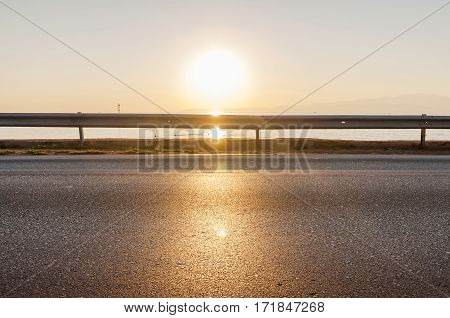 Road and sea in sunset time with burrning sun