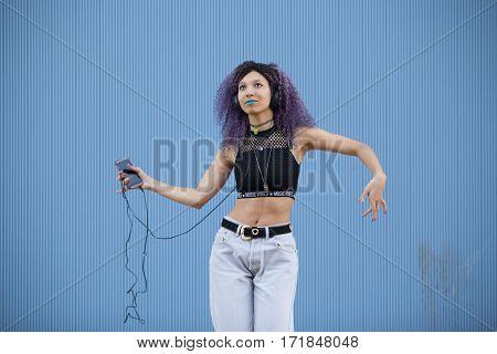 interracial teenager listening to music with big headphones on a blue background
