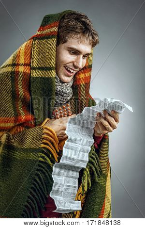 Happy sick man covered in blanket reads to instructions. Photo of man suffering cold and flu virus. Health care concept