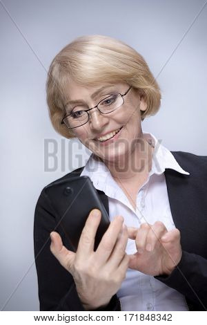 Beautiful Matured Woman happy cheerful caucasian in glasses toothy smile blond studio shot looking at telephone.  Calling mobile telephone. mobile payments. Grey background