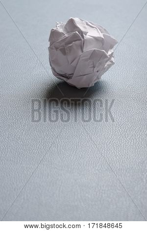 crumpled-up ball of paper on desk pad with copy space