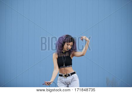 interracial teenager dancing to the music isolated on a blue background