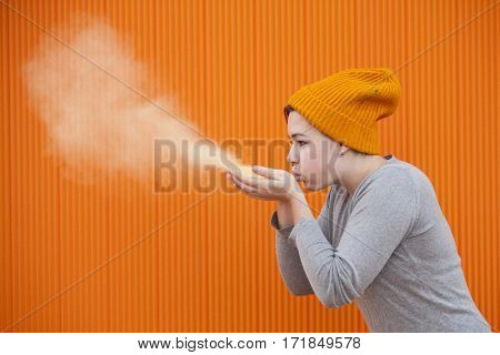 teen woman blowing a colored dust cloud isolated on an orange background