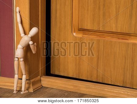Curiosity overcomes fear. Wooden lay figure looks at the slightly opened door.