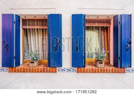 Picturesque windows with blue shutters and flowers on light pink wall of houses on the famous island Burano, Venice, Italy