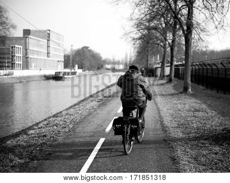 Rear view of man on his bicycle cycling fast near Ill river to the center of Strasbourg on the dedicated bicycle lane - black and white photo