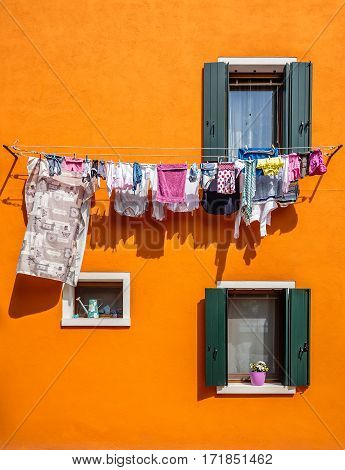 Drying clothes on the rope on the orange wall with two windows with shutters of house in Burano,Venice.