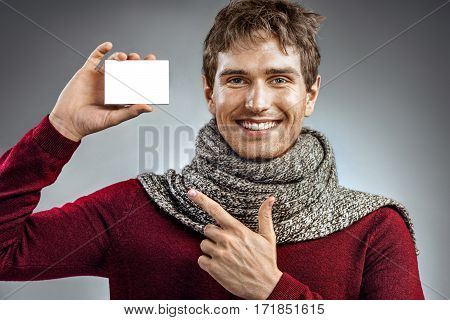 Smiling man wrapped in scarf holding box for medicine. Photo of unhealthy man pointing finger at white packaging for medicine. Healthcare concept