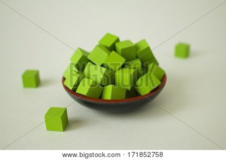 Green cubes piled up in a dish.