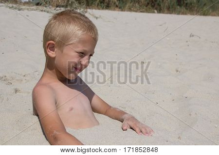 Boy buried in sand on the beach