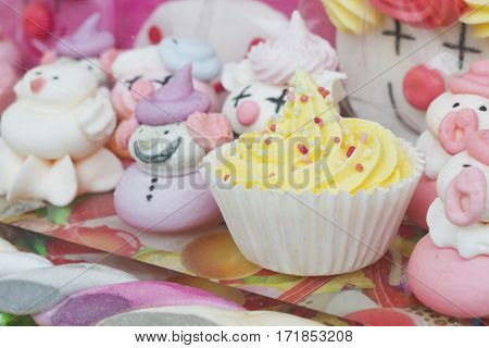 Small yellow cupcake on a glass shelter among candies.