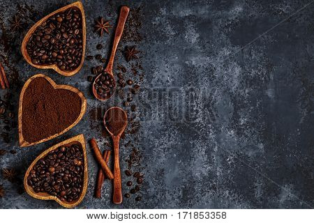 Top view of coffee beans, ground coffee and spices on dark background.