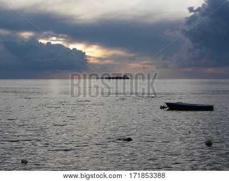 Warm sea sunset with cargo ship at the horizon . Giants cumulonimbus clouds are in the sky. Tuscany Italy