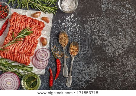 Raw minced meat on paper with onion, herbs and seasonings on black background, top view.
