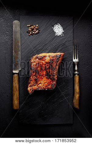 grilled beef on a black stone, knife, fork and salt