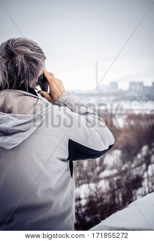 An elderly man talking on the phone and looking at plant close-up. Old man outdoors European Caucasian winter on a cloudy day