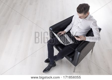 Top view of a young businessman sitting in a large leather armchair with a laptop and a cell phone. Concept of technology and business.